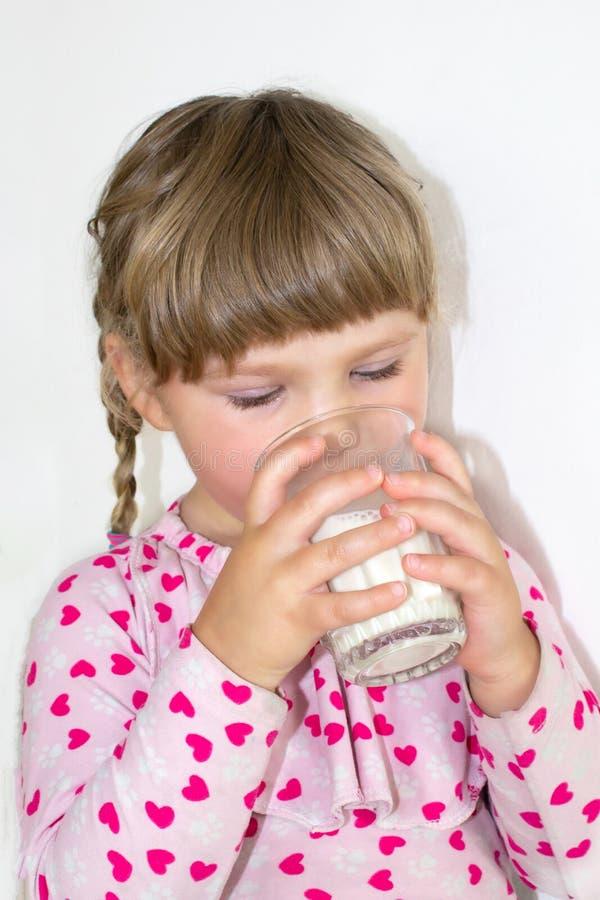 Liten flickadrinkarna mjölkar, mjölkar fördelarna av och kalcier för barn Ett barn av tre år royaltyfri fotografi