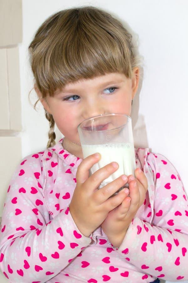 Liten flickadrinkarna mjölkar, mjölkar fördelarna av och kalcier för barn Ett barn av tre år arkivbilder