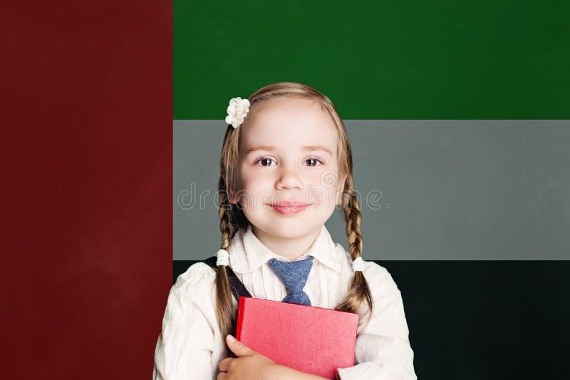 Liten flickaelev med boken mot den Förenade Arabemiraten flaggabakgrunden royaltyfri foto
