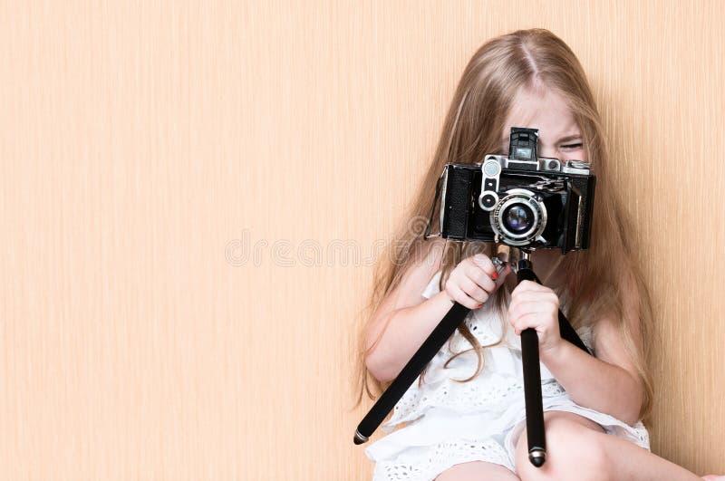 Liten flickaforsar på kamera royaltyfri bild
