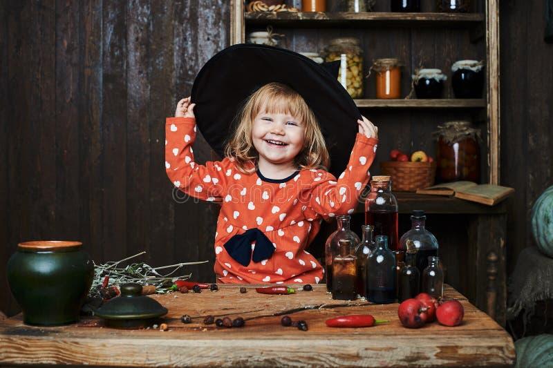Liten flickahäxan i svart pekade hatten och magisk tillbehör Allhelgonaafton studioaftonen royaltyfri fotografi