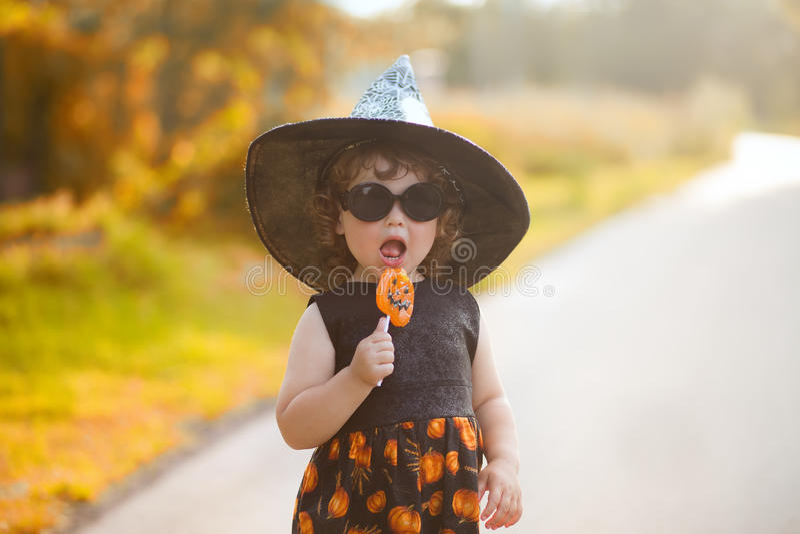 Liten flickahäxan i svart pekade hatten och solglasögon arkivbild