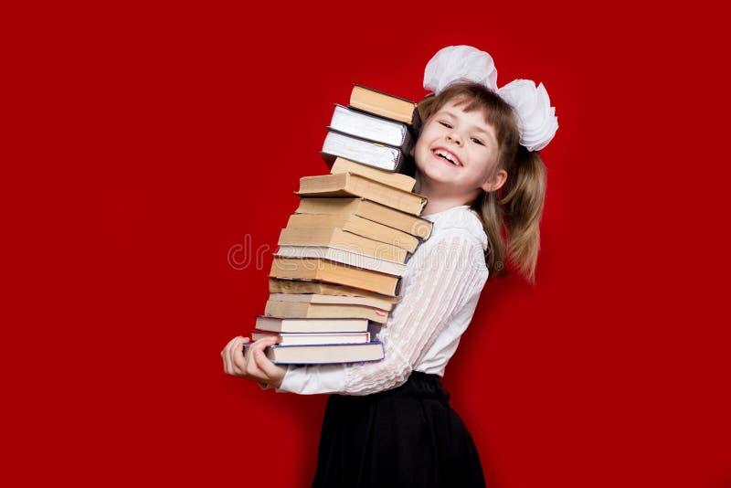 Liten flickahåll många böcker som isoleras på rött royaltyfri fotografi