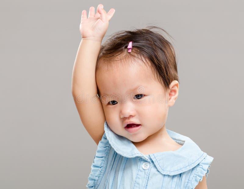 Liten flickahanden lyfter upp arkivfoto