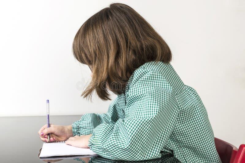 Liten flickahandstil i en anteckningsbok fotografering för bildbyråer
