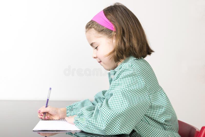Liten flickahandstil i en anteckningsbok royaltyfria bilder