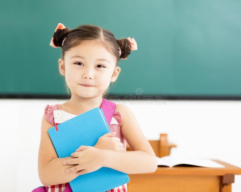 liten flickainnehavbok i klassrum royaltyfria bilder