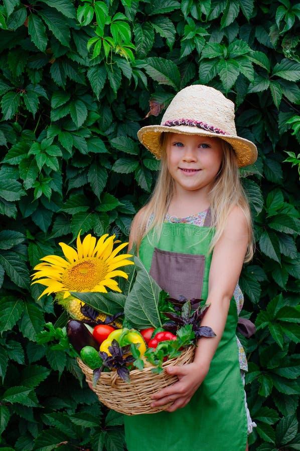 Liten flickainnehavkorg med nya grönsaker royaltyfri bild