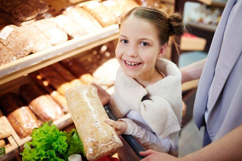 Liten flickaköpandelivsmedel i supermarket royaltyfri bild
