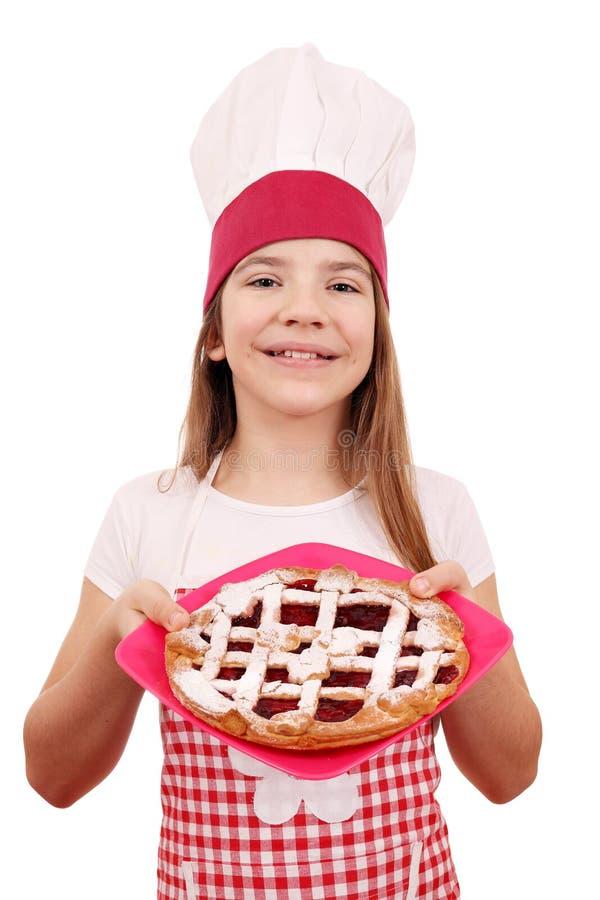 Liten flickakock med den körsbärsröda pajen på plattan arkivbild