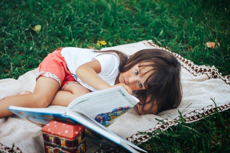 Liten flickalögn på gräs och läseboken arkivfoto