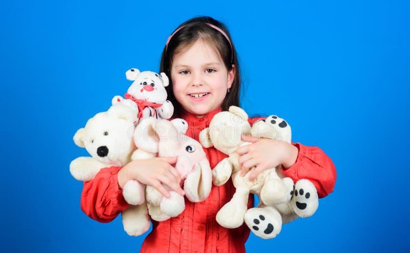 Liten flickalek med den mjuka leksaknallebj?rnen Lott av leksaker i hennes h?nder Barndombegrepp Samla leksakerhobby royaltyfri fotografi