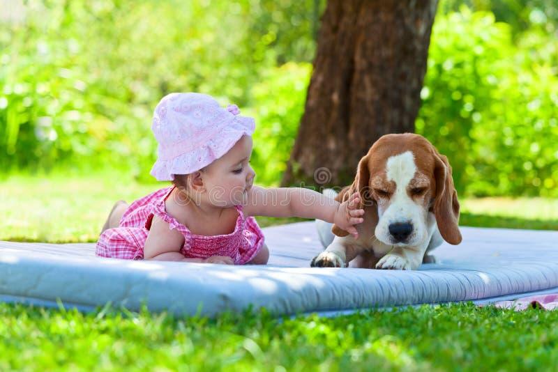 Liten flickalekar med hunden arkivbilder