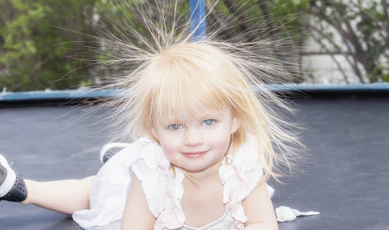 Liten flickalilla barnet spelar på en trampolin och har statisk elektricitet i hennes hår arkivfoton