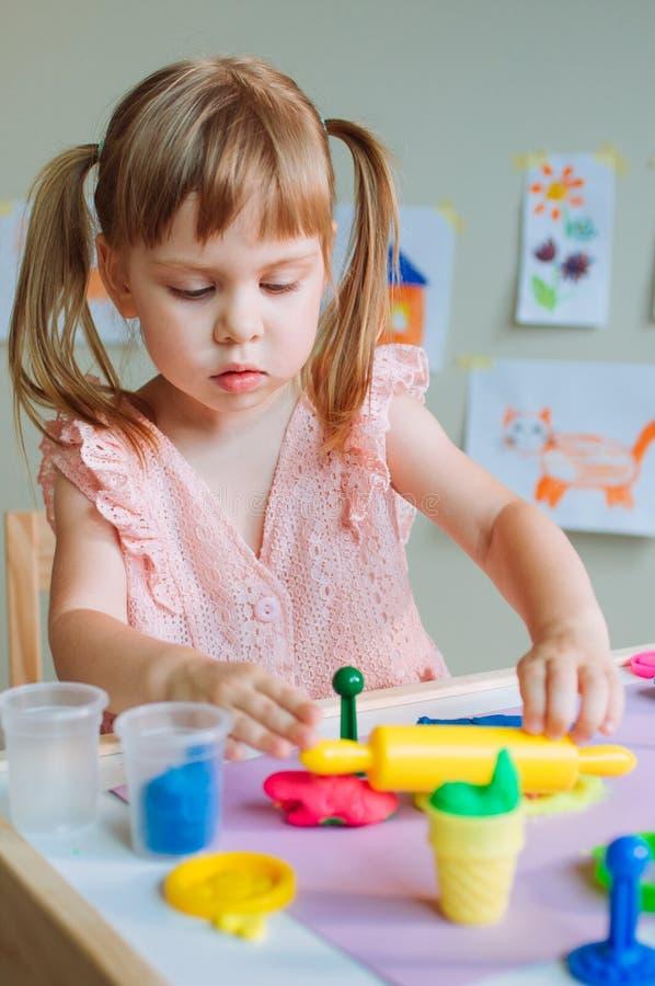 Liten flickalitet barn som gjuter färgrik lera på tabellen arkivfoto