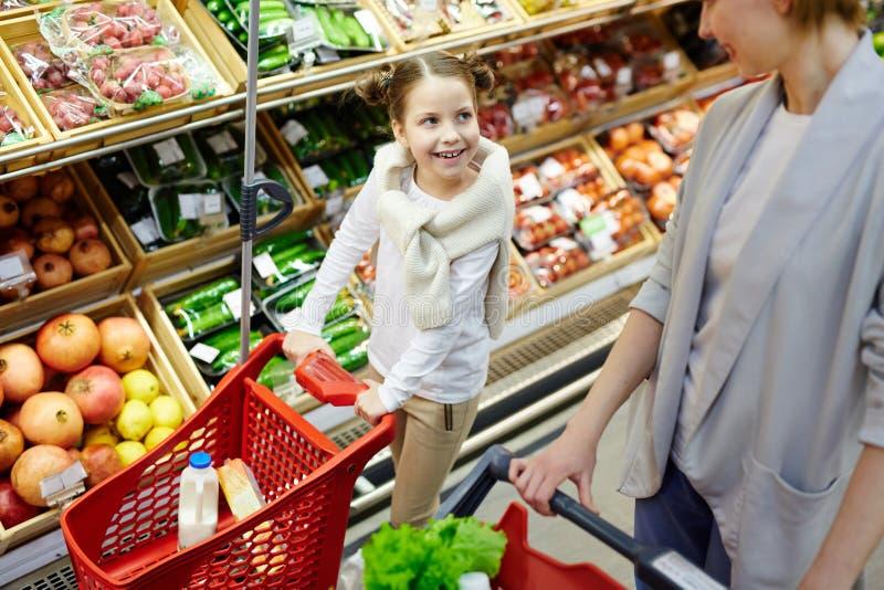 Liten flickalivsmedelsbutikshopping i supermarket royaltyfri bild