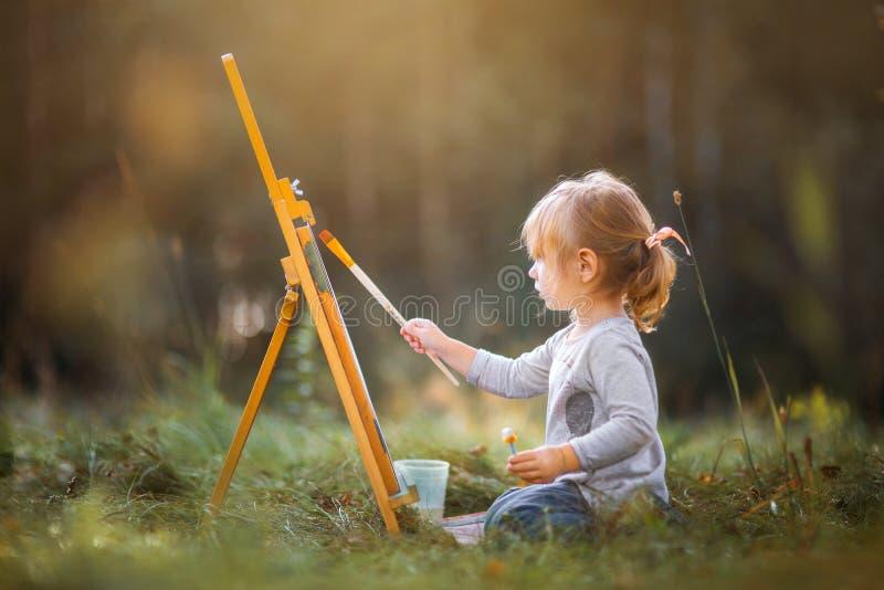 Liten flickamålning utomhus arkivfoto
