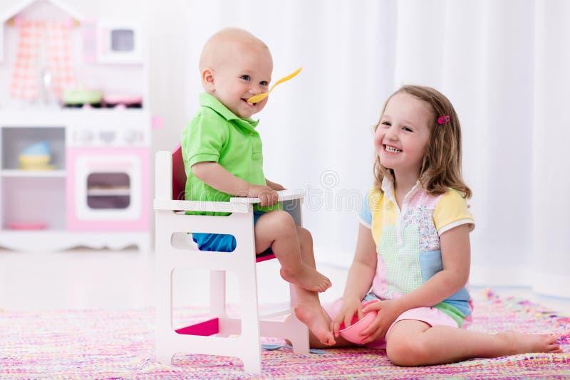 Liten flickamatning behandla som ett barn brodern royaltyfri fotografi