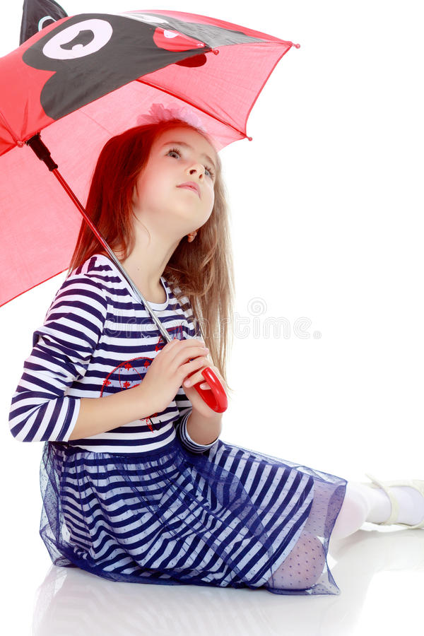 Liten flickanederlag under ett paraply arkivfoton
