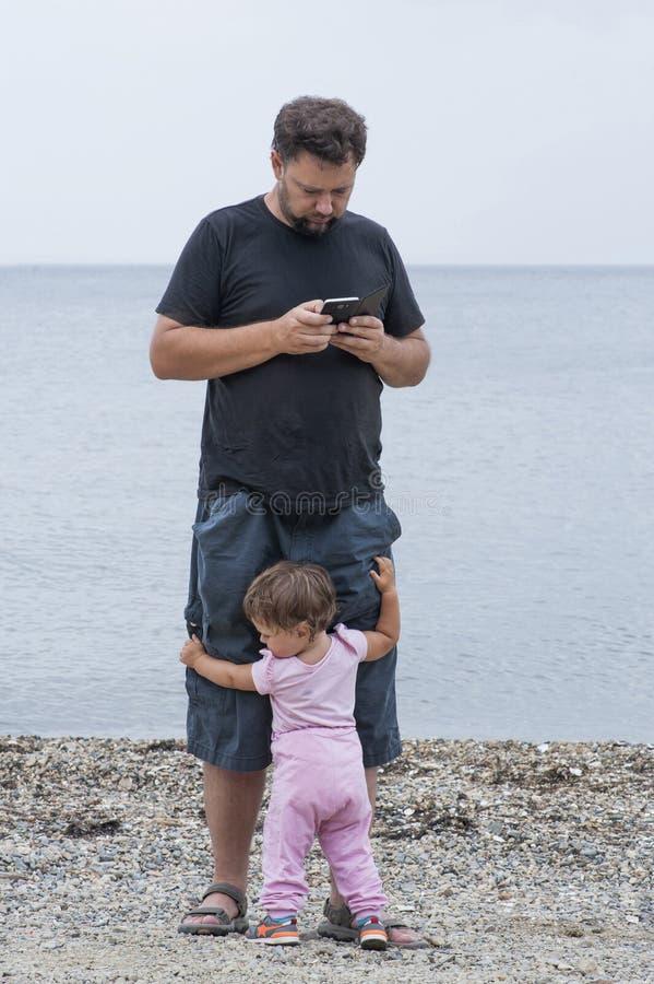 Liten flickaomfamning till farsan medan honom som är upptagen med telefonen royaltyfria foton