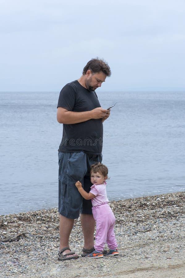 Liten flickaomfamning till farsan medan honom som är upptagen med telefonen royaltyfri foto