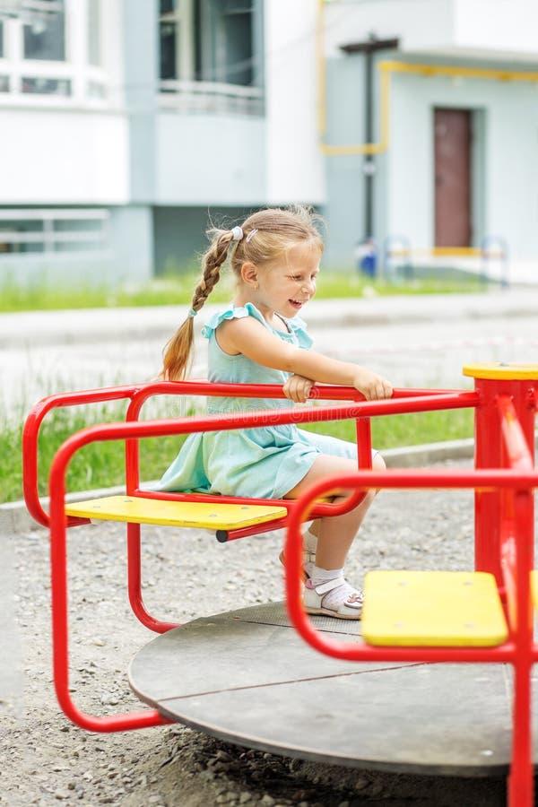 Liten flickaritt på karusellen Begreppet av barndom, livsstil, uppfostran, dagis royaltyfria bilder