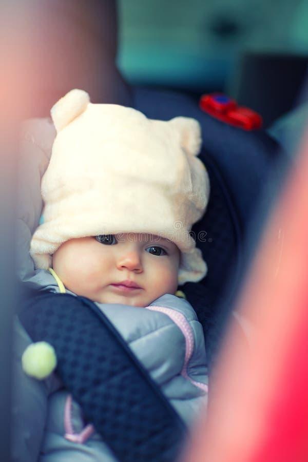 Liten flickasammanträde i bil i vinterkläder arkivbilder