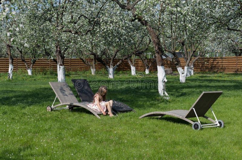 Liten flickasammanträde i blomningäppleträdgård placera att koppla av arkivfoto