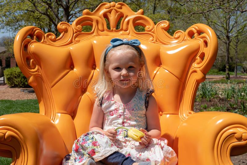 Liten flickasammanträde i en ljus orange stol i en trädgård arkivbilder