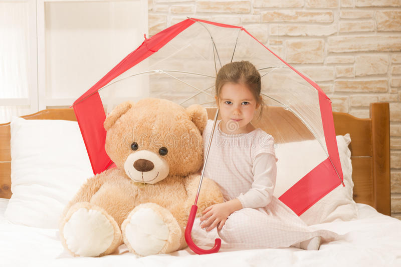 Liten flickasammanträde i säng under paraplyet med hennes nallebjörn arkivbild