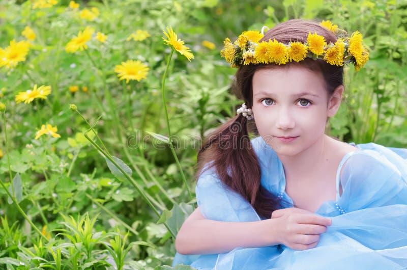 Liten flickasammanträde på blommaäng royaltyfria foton