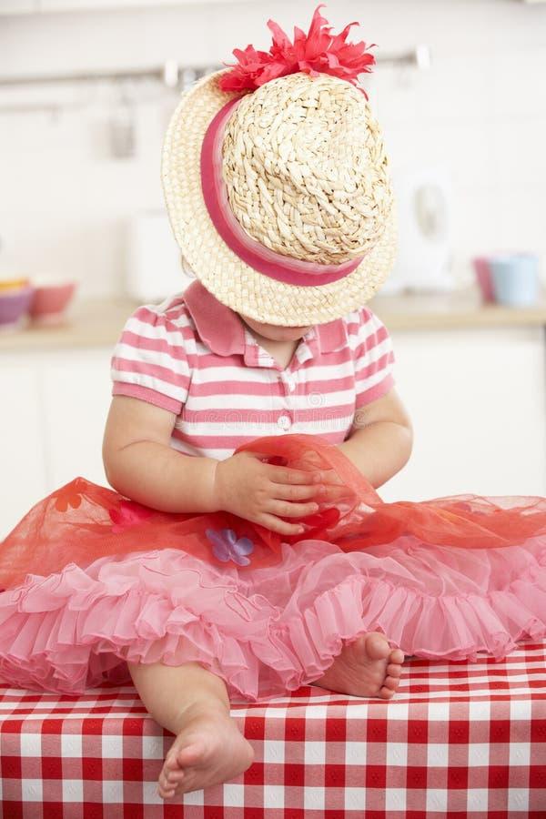 Liten flickasammanträde på den bärande hatten för köksbord royaltyfria bilder