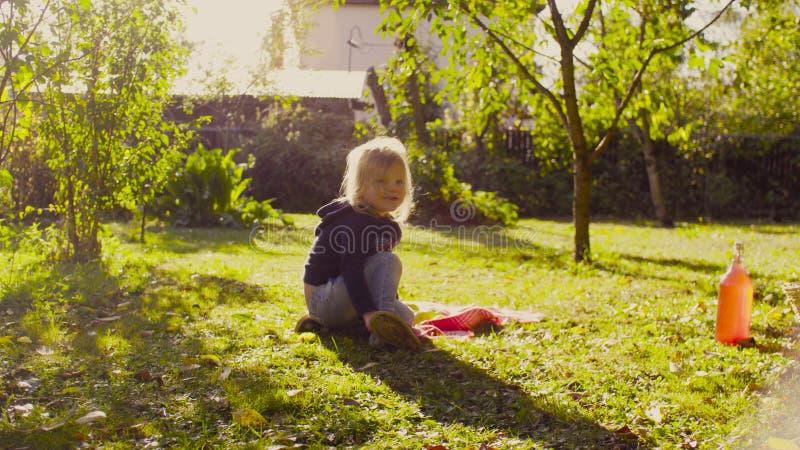 Liten flickasammanträde på ett gräs i en trädgård och sätta på hennes skor arkivfoton