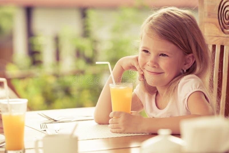 Liten flickasammanträde på frukosten royaltyfria bilder