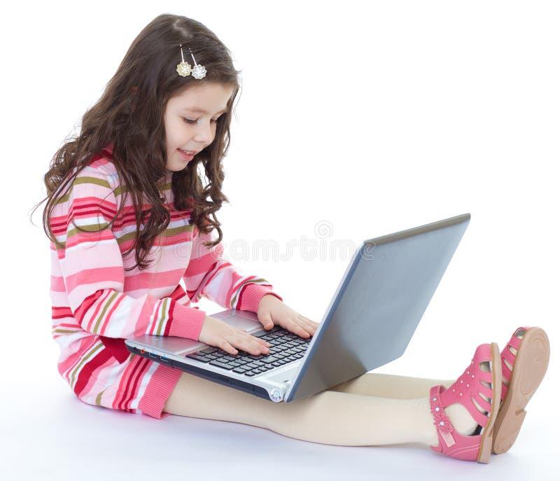 Liten flickasammanträde på golvet med en bärbar dator. arkivbilder