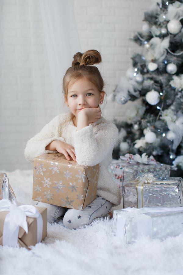 Liten flickasammanträde på golvet nära julgranen med julgåvan i händer royaltyfri foto