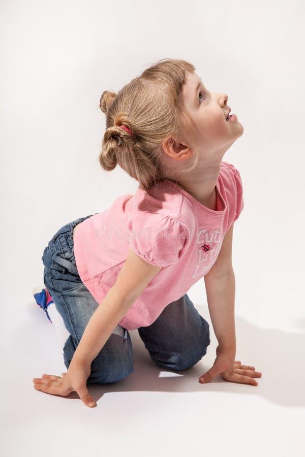 Liten flickasammanträde på golvet och se upp royaltyfri bild
