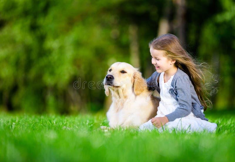 Liten flickasammanträde på gräset med hunden royaltyfria bilder