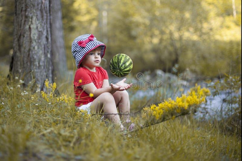 Liten flickasammanträde på gräset och spela med vattenmelon royaltyfria foton