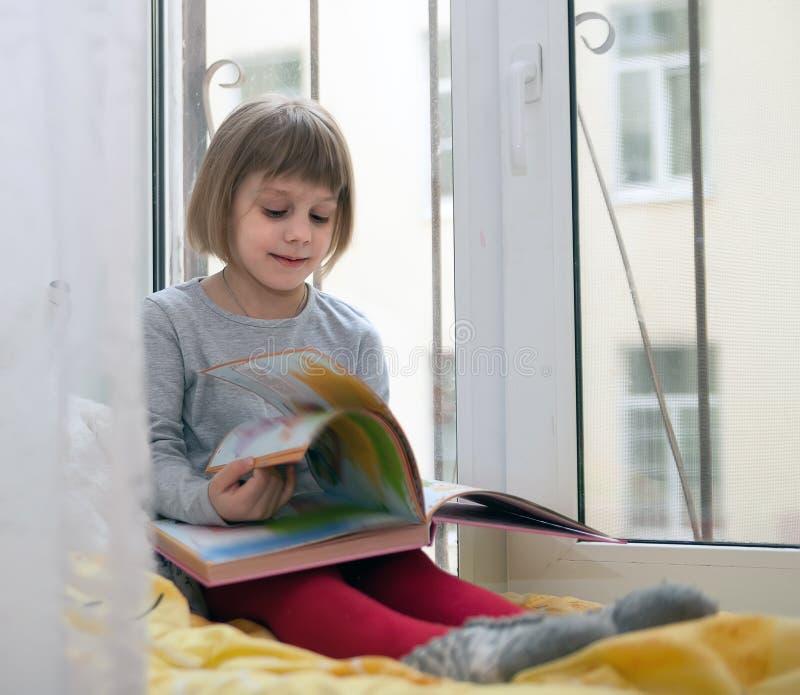Liten flickasammanträde på hemtrevlig fönster-fönsterbräda royaltyfria foton