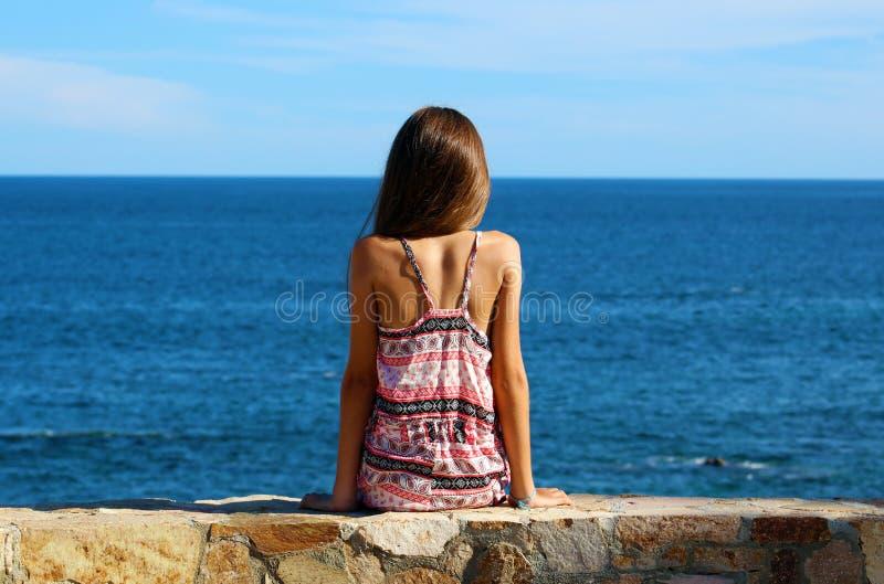 Liten flickasammanträde på klippan på havframdelen i havet för Los Cabos Mexico semesterortklippa arkivbild