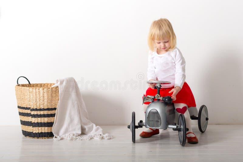 Liten flickasammanträde på retro leksakbilar i ett rum på en vit bakgrund fotografering för bildbyråer