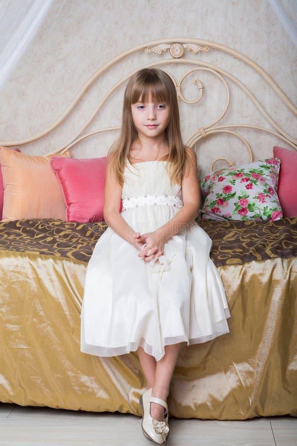 Liten flickasammanträde på sängen royaltyfri foto