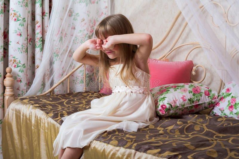 Liten flickasammanträde på sängen och rubsna hans ögon fotografering för bildbyråer