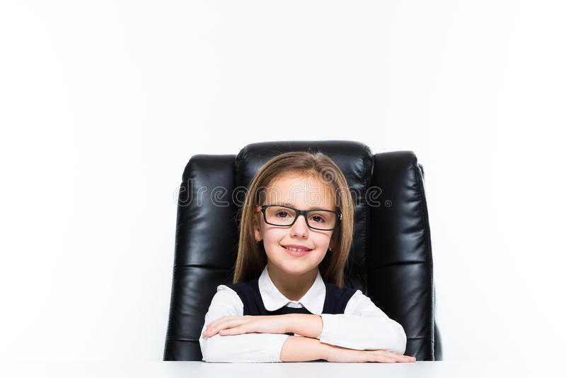 Liten flickasammanträde på skrivbordet på hennes arbetsplats klädde som en affärskvinna arkivfoton