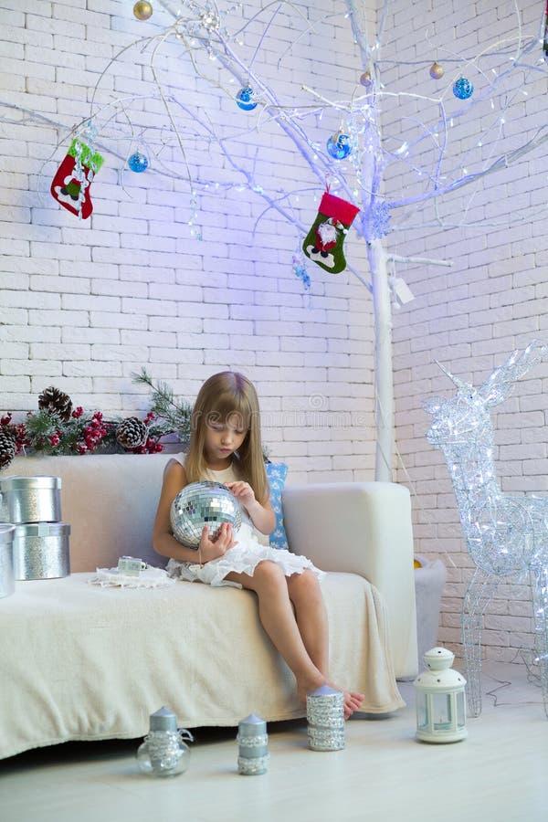 Liten flickasammanträde på soffan med gåvor och att spela för jul arkivfoto