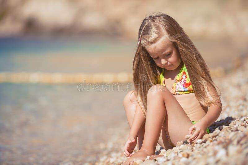 Liten flickasammanträde på stranden nära havet arkivfoto