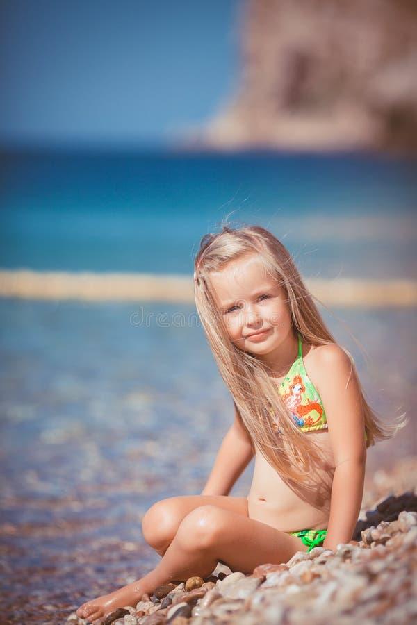 Liten flickasammanträde på stranden nära havet arkivfoton