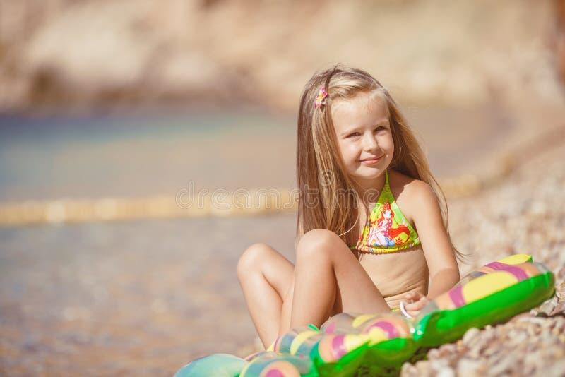 Liten flickasammanträde på stranden nära havet royaltyfri fotografi