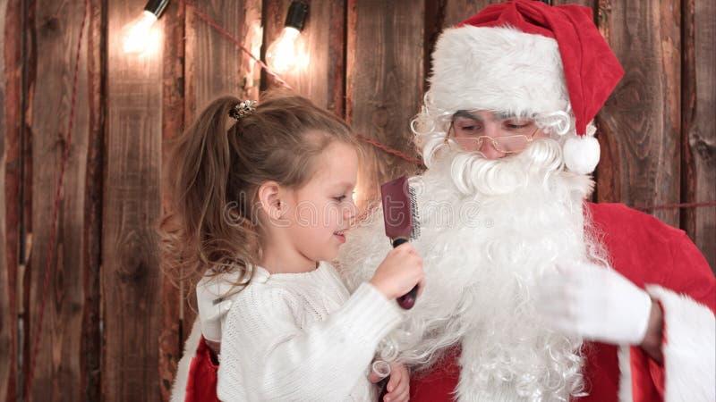 Liten flickasammanträde på varven av gammal jultomten och att borsta hans skägg royaltyfria bilder